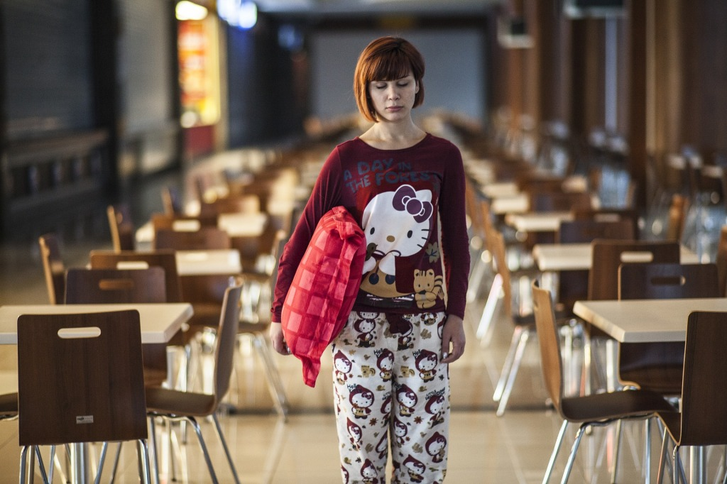 woman in pyjamas sleepwalking through a cafeteria to show lack of conscious living and mindfulness